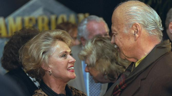 """FILE - In this Tuesday Dec. 10, 1996 file photo, star of the 1963 Alfred Hitchcock film """"The Birds"""", Tippi Hedren greets 1940's motion picture actor Turhan Bey at the world premiere screening of """"20th Century Fox: The First 50 Years"""" in Los Angeles. Turhan Bey, who starred in Hollywood escapist fantasies with the likes of Errol Flynn and Katherine Hepburn, has died at age 90. His death in Vienna was announced Tuesday Oct. 9, 2012, by Marita Ruiter, a close acquaintance. (AP Photo/Chris Pizzello, File)"""