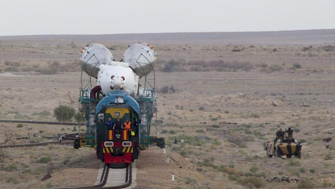The Soyuz TMA-18M spacecraft is transported from an assembling hangar to its launch pad at the Baikonur cosmodrome, Kazakhstan