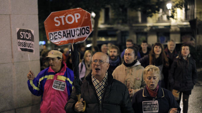 """People hold banners that read: """"Stop Evictions"""", during a march against evictions, in Madrid, Friday, Nov. 9, 2012. Officials say a woman fell to her death as bailiffs approached to evict her for non-payment of the mortgage from her fourth-floor apartment in a suburb of the northern Spanish city of Bilbao. Amaia Egana, 53-year-old, who worked at a local bus depot, was married to a former town councilor and had a 21-year-old daughter, launched herself off her balcony Friday, the regional Interior Ministry said. (AP Photo/Andres Kudacki)"""