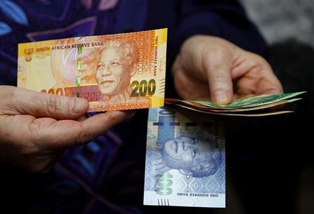 South African Reserve Bank Governor Gill Marcus shows off South Africa's new banknotes before conducting the first transaction in Pretoria