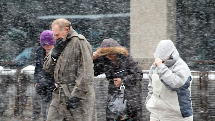 Pedestrians brace against the cold and snow as they walk throught the 16th Street Mall during the noon hour in Denver on Wednesday, April 17, 2013. As much as five inches of new snow is forecast for Denver. (AP Photo/Ed Andrieski)