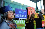 A Brazilian Tapuya (L) native takes part in a protest against the government decision to authorize actions inside indigenous lands without the natives' permission in Brasilia on July 26. Violent disputes over indigenous land have been growing across Brazil, sparking heightened militancy by native tribes angered by broken promises of compensation and slower government registrations