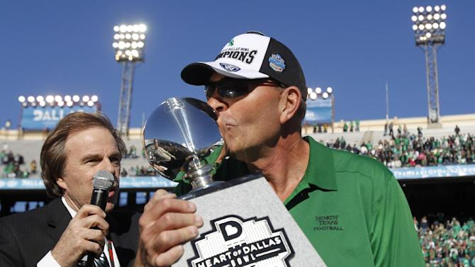North Texas head coach Dan McCarney kisses the Heart of Dallas Bowl trophy following their 36-14 win over UNLV in the Heart of Dallas NCAA college football game, Wednesday, Jan. 1, 2014, in Dallas