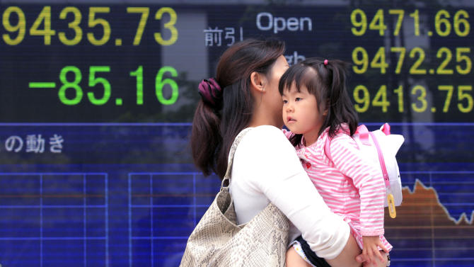 A woman and a child walk in front of the electronic stock board of a securities firm in Tokyo, Japan, Tuesday,  May 1, 2012. Japan's Nikkei 225 fell Tuesday amid a stronger yen and signs of a slowing U.S. economy, while other key Asian stock indexes were closed for a public holiday. (AP Photo/Itsuo Inouye)