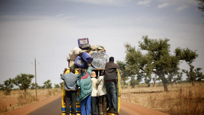 Malians hang on the back of a packed minibus as they drive to Marakala, central Mali, some 240kms (140 miles) from Bamako Tuesday, Jan. 22, 2013.  French troops in armored personnel carriers rolled through the streets of Diabaly on Monday, winning praise from residents of this besieged town after Malian forces retook control of it with French help a week after radical Islamists invaded. The Islamists also have deserted the town of Douentza, which they had held since September, according to a local official who said French and Malian forces arrived there on Monday as well. (AP Photo/Jerome Delay)