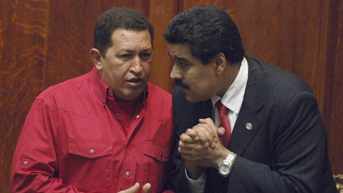 FILE - In this Dec. 18, 2007 file photo Venezuela's President Hugo Chavez, left, talks to then Foreign Minister Nicolas Maduro at the University of Uruguay in Montevideo, Uruguay.   Chavez is heading back to Cuba on Sunday Dec. 9, 2012 for more surgery for cancer, announcing on television that the illness has returned after two previous operations, chemotherapy and radiation treatment. Chavez acknowledged the seriousness of his situation in an address Saturday night, saying for the first time that if he suffers complications Vice President Nicolas Maduro should take his place as Venezuela's leader and continue his socialist movement.(AP Photo/Matilde Campodonico, File)