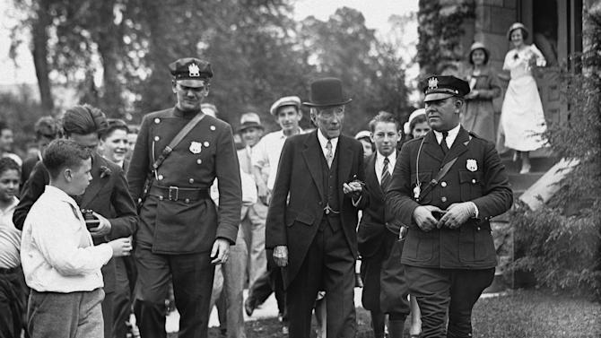 "FILE - In this May 14, 1933 file photo, John D. Rockefeller, Sr. is surrounded by state troopers and admirers as he attended church in Lakewood, N.J. In the early 21st century, members of the economic elite are looking for ways to reduce the nation's growing income inequality for a variety of reasons, from self-interest to pangs of conscience. ""Names like Carnegie, Mellon and Rockefeller_ the (Warren) Buffet and (Bill) Gates of their days - grace universities, museums and medical centers in part because the originators of those fortunes gave back,"" Harvard Business School professor Michael Norton says. (AP Photo, File)"