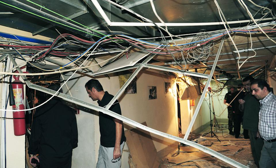 In this photo released by the Syrian official news agency SANA, Syrians inspect the scene after a bomb ripped through the third floor of the state TV building in Damascus, Syria, on Monday, Aug. 6, 2012. The bomb shattered several offices and wounded several employees, Syrian TV said. (AP Photo/SANA)