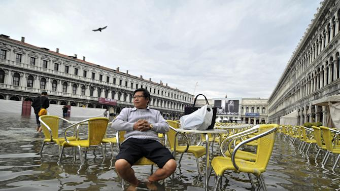 FILE - A tourist sits outside a cafe in a flooded St. Mark square as high tides reached 1.05 meters above sea level, partly flooding the city of Venice, Italy on Monday, Oct. 15, 2012. The Lagoon City, a system of islands built into a river delta, is extremely vulnerable to rising sea levels. At the same time it is experiencing a lowering of the sea floor. The constant flooding puts the city's considerable architectural treasures at risk. (AP Photo/Luigi Costantini)