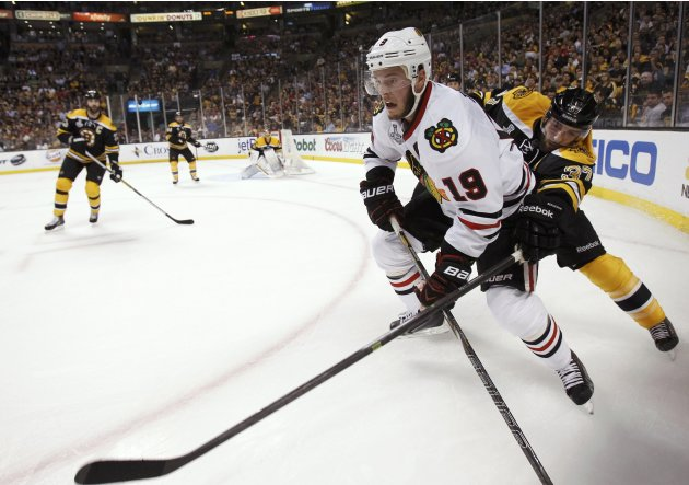 Blackhawks' Toews is checked from behind by Bruins' Bergeron during the first period in Game 4 of their NHL Stanley Cup Finals hockey series in Boston