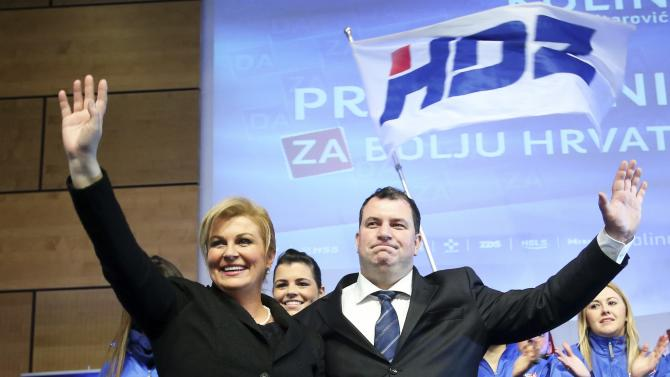 Presidential candidate of HDZ party Kolinda Grabar-Kitarovic with husband Jakov Kitarovic wave to supporters after unofficial results in Zagreb