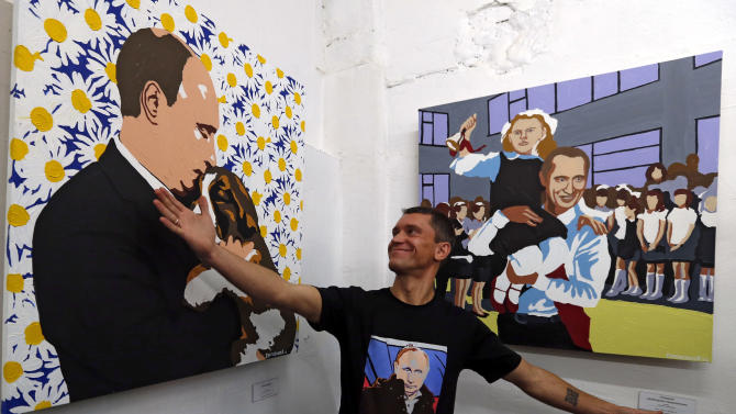 "Artist Alexei Sergiyenko gestures in front of his paintings of Russian President Vladimir Putin during the opening of his exhibition ""President. The kindest person"" at the Flacon design workshop in Moscow, Sunday Oct. 7, 2012. Vladimir Putin turns 60-years old on Sunday, Oct. 7, 2012, and has recently sought to demonstrate his youthful vigor by many personal endeavors, but while he has shown creativity in his action-man stunts, the Russian president seems surprisingly vulnerable to the vagaries of oil prices. (AP Photo/Sergey Ponomarev)"