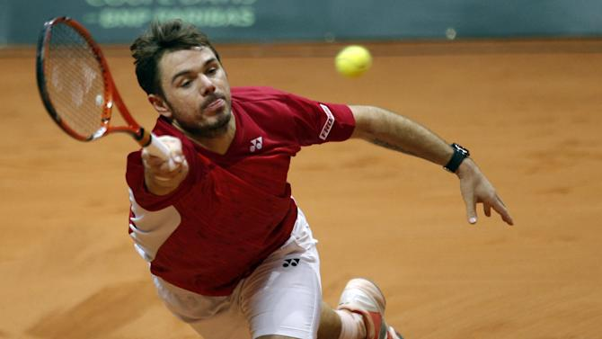 Switzerland's Stanislas Wawrinka returns the ball to France's Jo-Wilfried Tsonga during the  Davis Cup final in Lille, northern France, Friday, Nov.21, 2014. Switzerland is seeking a first victory in the team competition while France is looking for a 10th title. This is the 13th meeting between the two nations, with France leading 10-2. (AP Photo/Peter Dejong)