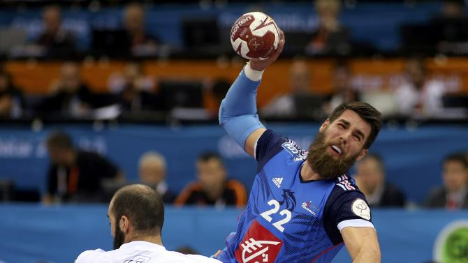 Karabatic of France attempts to score past Querin of Argentina during their round of 16 match of the 24th men's handball World Championship in Doha