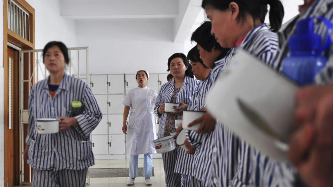 In this May 11, 2012 photo, a nurse administers patients, who are lining up before lunch, at a psychiatric hospital in Zouping county, in eastern China's Shandong province. China's legislature on Friday, Oct. 26, 2012, passed a long-awaited mental health law that aims to prevent people from being involuntarily held and treated in psychiatric facilities - abuses that have been used against government critics and have triggered public outrage. (AP Photo)  CHINA OUT