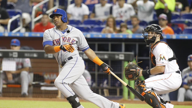 New York Mets batter Yoenis Cespedes hits a first inning double in front of Miami Marlins catcher J.T. Realmuto during a baseball game in Miami, Monday Aug. 3, 2015. (AP Photo/Joe Skipper)