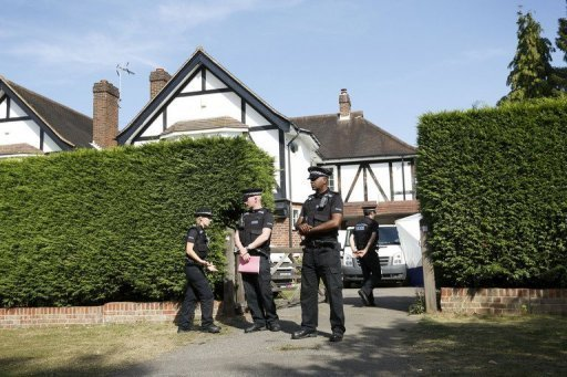 <p>British police stand outside the Claygate home of a family shot dead in their car in the French Alps. French police were on Monday waiting to question a young British girl seen as the key to solving the mystery of the shooting that left three members of her family and a cyclist dead.</p>