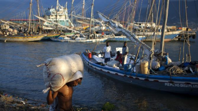 In this Monday, Dec. 3,  2012, a worker carries a sack along the shoreline of Wharf Jeremie, Port-au-Prince, Haiti. Haitians suffered widespread hunger following an unusually active storm season this year and are likely to experience more, according to a study released Friday, Dec. 7, 2012. Nearly 70 percent of the more than 1,000 households interviewed said they experienced moderate or severe hunger, the study found.  (AP Photo/Dieu Nalio Chery)
