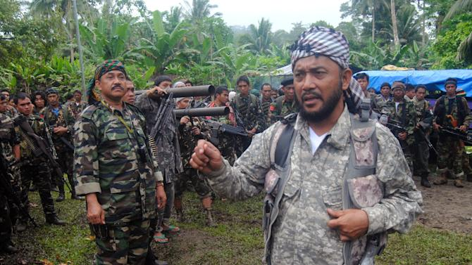 FILE - In this Jan. 15, 2013 file photo, Khabir Malik, Commander of the Moro National Liberation Front, a Muslim rebel group which signed a 1996 peace pact with the Philippine government briefs his comrades at Patikul township, on the volatile island of Jolo in southern Philippines. After years of fighting the government from hidden jungle bases in the southern Philippines, an Al-Qaida-linked militant group is facing a new adversary: fellow Muslim insurgents who can match their guerrilla battle tactics and are eager to regain their lost stature by fighting the widely-condemned terrorist group. The emerging enmity between the Abu Sayyaf militants and the Moro rebels could bolster a decade-long campaign by the Philippines and Western countries to isolate the al-Qaida offshoot Abu Sayyaf, which remains one of the most dangerous groups in Southeast Asia.(AP Photo/Nickee Butlangan File)