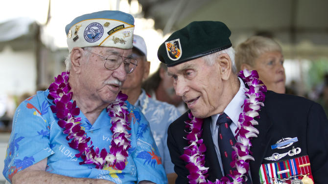 Pearl Harbor survivor Sam Clower, left, of Sacramento, Calif. and Ab Brum, right, , retired United States Army Special Forces, of Kaneohe, Hawaii, share memories of the Japanese attack on Pearl Harbor Friday, Dec. 7, 2012, at Pearl Harbor, Hawaii. Many of the Pearl Harbor Veterans gathered at the World War II Valor In The Pacific National Monument remembering the 71th anniversary of the Dec. 7, 1941 Japanese surprise attack on Pearl Harbor in Honolulu. (AP Photo/Eugene Tanner)