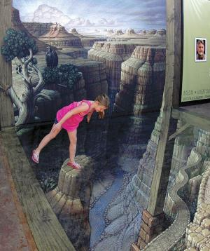 """This June 15, 2012 photo released by the National Geographic Visitor Center at Grand Canyon shows an unidentified visitor examining the sidewalk artwork """"Grand Canyon Illusion"""" by artist Kurt Wenner outside the National Geographic Visitor Center at the South Rim of the Grand Canyon near Tusayan, Ariz., in this handout photo made on June 15, 2012. The 3-D piece gives the illusion of being perched atop spires and starting down a winding trail that seemingly plunges into the depths of the massive gorge. (AP Photo/National Geographic Visitor Center at Grand Canyon, Joel Kramer)"""