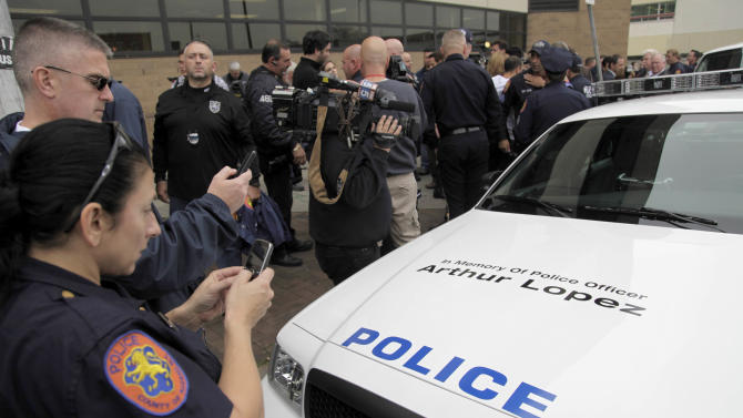Police officers take pictures of a car with Arthur Lopez's name on the hood after the arraignment of Darrell Fuller in Hempstead, N.Y., Thursday, Oct. 25, 2012.  Fuller, the ex-convict suspected of gunning down Lopez, a New York police officer, and then fatally shooting a carjacking victim, is charged with first-degree murder.  (AP Photo/Seth Wenig)