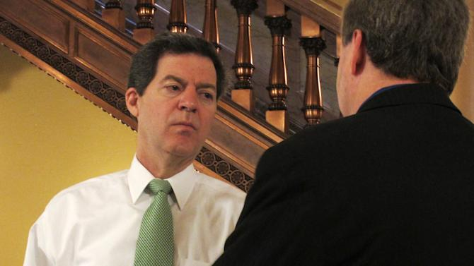 Kansas Gov. Sam Brownback, left, talks to state Rep. Steve Huebert, right, a Valley Center Republican, in a Statehouse hallway, Tuesday, March 20, 2012, in Topeka, Kan. Brownback says he's encouraged that a pensions bill passed by the House creates an optional 401(k)-style plan for new public employees, and Huebert supports the measure. (AP Photo/John Hanna)