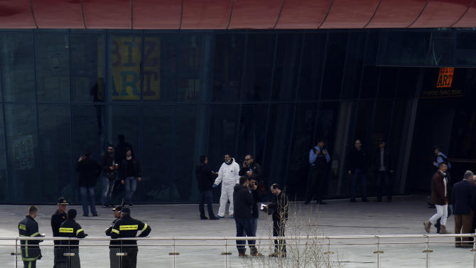 Security officers and firefighters stand outside a mall following a blast in Athens, Sunday, Jan. 20 2013. A bomb exploded Sunday at a shopping mall in Athens, slightly wounding two security guards, police said. (AP Photo/Kostas Tsironis)