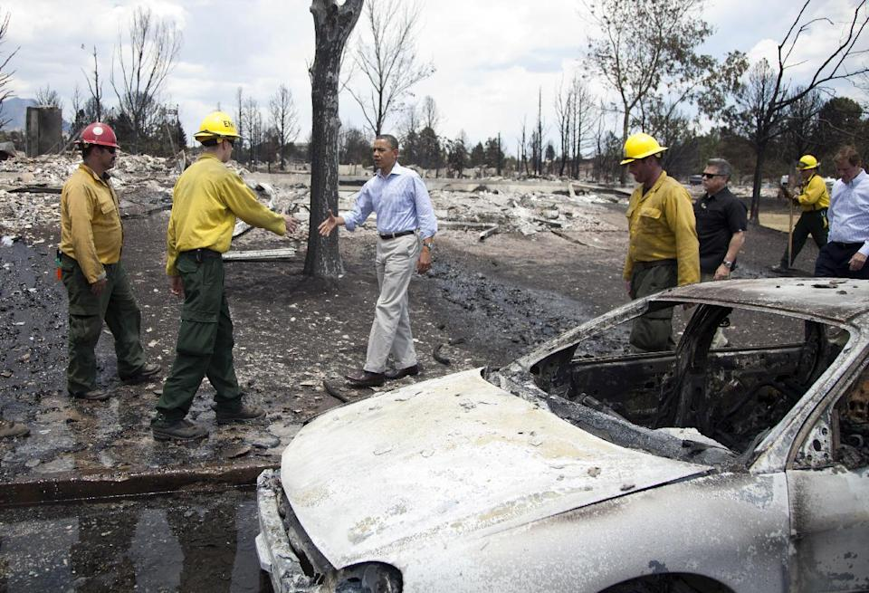 President Barack Obama walks past a burned out car to talk to firefighters as he tours the Mountain Shadow neighborhood devastated by raging wildfires, Friday, June 29, 2012, near, Colorado Springs, Colo. (AP Photo/Carolyn Kaster)