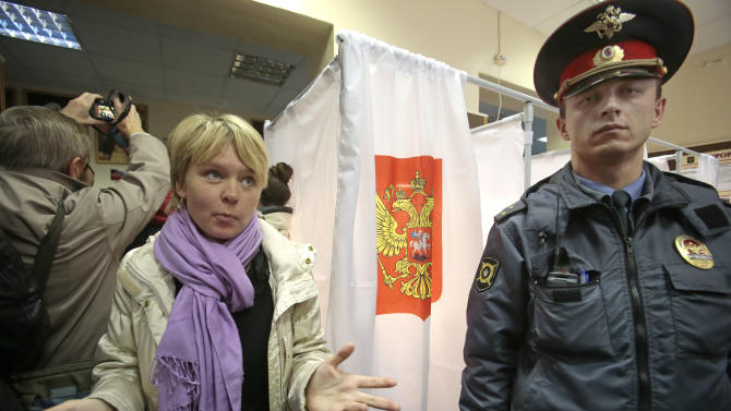 Opposition activist Yevgenia Chirikova, left, visits a polling station in the town of Khimki outside Moscow, Russia, Sunday, Oct. 14, 2012. Chirikova who played a major role in the massive winter protests against Putin's rule, is challenging the incumbent mayor. She has complained of an uneven playing field, saying authorities tried to thwart her meetings with voters and put up other obstacles. (AP Photo/Mikhail Metzel)