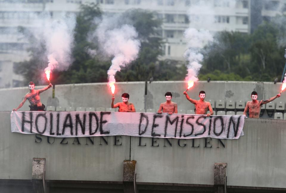 Demonstrators display a banner demanding the resignation of French President  Francois Hollande, atop Suzanne Lenglen court, as Spain's Rafael Nadal plays compatriot David Ferrer on center court during the men's final match of the French Open tennis tournament at the Roland Garros stadium Sunday, June 9, 2013 in Paris. (AP Photo/David Vincent)