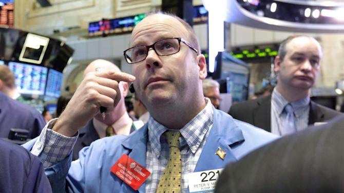 Trader Peter Mancuso, center, works on the floor of the New York Stock Exchange Wednesday, Feb. 6, 2013. Strong earnings reports from media giants Disney and Time Warner aren't impressing investors in early trading, and major U.S. market indexes are opening lower. (AP Photo/Richard Drew)