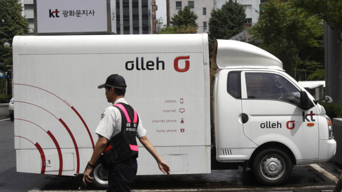 A police officer passes by a vehicle advertising KT, South Korea's largest fixed-line telephone company and No. 2 mobile operator, at the company's branch office in Seoul, South Korea, Monday, July 30, 2012. South Korean police Sunday said they arrested two men who allegedly stole the personal details of about 8 million KT mobile phone subscribers and sold the data to marketing companies in one of the country's biggest hacking schemes.(AP Photo/Ahn Young-joon)