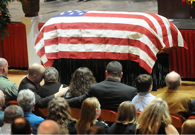 "Family members embrace during the funeral service of Charles ""Chuck"" Poland in Ozark, Ala., Sunday, Feb. 3, 2013. Authorities say Jim Lee Dykes, 65 — a decorated veteran of the Vietnam War known as Ji"