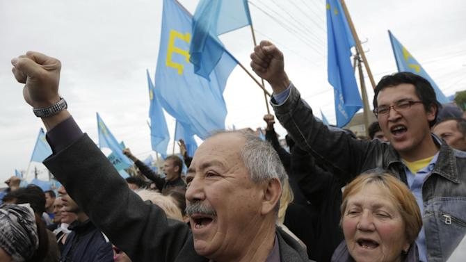 Crimean Tatars chant slogans as they rally in Simferopol, Crimea, Sunday, May 18, 2014. Crimean Tatars gathered for a rally commemorating the 70th anniversary of Stalin's mass deportation. (AP Photo/Max Vetrov)