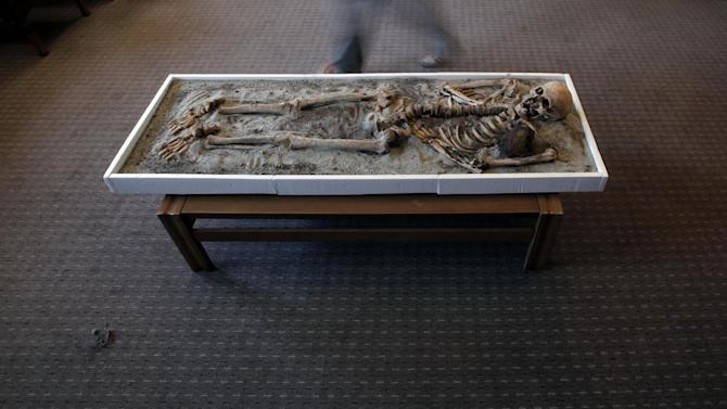 A long exposure photo shows a man passing a displayed skeleton dating back to the Middle Ages and recently unearthed in the black sea town of Sozopol, at National History Museum in  Sofia, Thursday, June 14, 2012. Ever since archaeologists announced last week that they had found two ancient skeletons in Bulgaria with iron rods thrust through their chests, the media have been reporting how Bulgarians once did that to prevent the dead from emerging from the grave as vampires. On Saturday, one of those 700-year-old skeletons will be put on display at the National History Museum in Sofia, and its director, Bozhidar Dimitrov, says he expects there to be a big turnout.  (AP Photo/Valentina Petrova)