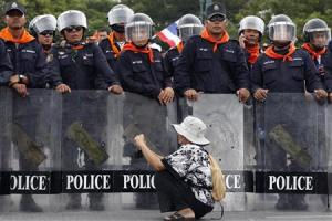 A woman takes pictures in front of a line of policemen blocking protesters against an amnesty bill, on the main road near the government and parliament buildings in central Bangkok