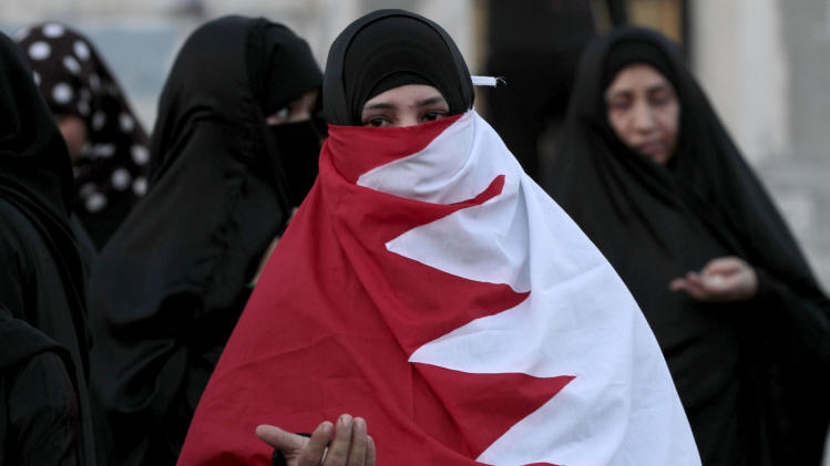 Bahraini anti-government protesters, one wrapped in a national flag, pray at the end of a small demonstration in Karzakan, Bahrain, on Saturday, Oct. 13, 2012, for the release of residents of the western village jailed in connection with unrest in the Gulf island kingdom. (AP Photo/Hasan Jamali)