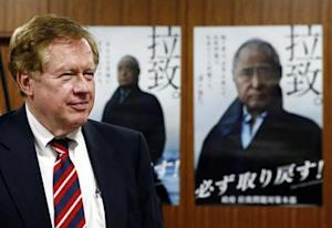 Robert King, U.S. special envoy for North Korean human rights issues, stands in front of campaign posters during a meeting in Tokyo