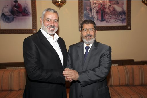 Egypt's president Mohamed Mursi shakes hands with Senior Hamas leader Ismail Haniyeh after their meeting at the presidential palace in Cairo
