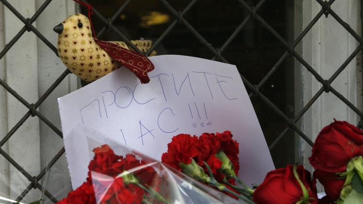 A note is seen with flowers placed outside the Dutch embassy in Moscow