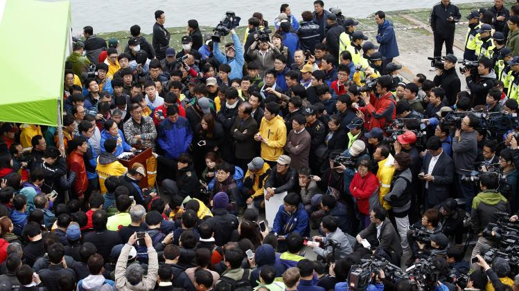 "Family members of missing passengers, who were on the South Korean ferry ""Sewol"" which sank at sea, listen along with media to a briefing from an official from the Korea Coast Guard about a rescue and search operation at a port in Jindo"