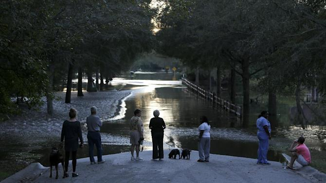 Residents look down Mayfield St. as the Ashley river floodwaters rise in the Ashborough subdivision near Summerville, S.C., Tuesday, Oct. 6, 2015. Residents are concerned that the Ashley river will continue to rise as floodwaters come down from Columbia. (AP Photo/Mic Smith)