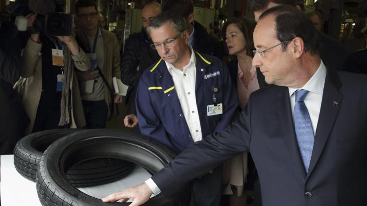 French President Hollande speaks with a worker as he visits French tyremaker Michelin factory in La Doux near Clermont-Ferrand