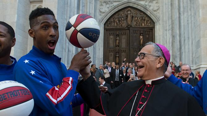 Bishop Dominick Lagonegro spins a basketball on his finger with the help of the Harlem Globetrotters in front of St. Patrick's Cathedral during the Columbus Day Parade on Fifth Ave. in the Manhattan borough of New York