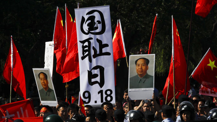 """Anti-Japan protesters hold portraits of the late Communist leader Mao Zedong, Chinese national flags, and a poster that reads: """"Sept. 18, National Humiliation Day,"""" while marching on a street outside the Japanese Embassy in Beijing Tuesday, Sept. 18, 2012. The 81st anniversary of a Japanese invasion brought a fresh wave of anti-Japan demonstrations in China on Tuesday, with thousands of protesters venting anger over the colonial past and a current dispute involving contested islands in the East China Sea. (AP Photo/Alexander F. Yuan)"""