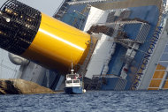 A police boat sails by the grounded cruise ship Costa Concordia, off the Tuscan island of Giglio, Italy, Sunday, Jan. 22, 2012. Rescuers on Sunday resumed searching the above-water section of the capsized Costa Concordia cruise liner, but choppy seas kept divers from exploring the submerged part, where officials have said there could be bodies. Civil protection officials said that until the waves slack off, divers would not swim into the submerged part of the vessel just off the port of Giglio, a tiny Island off the Tuscan coast. (AP Photo/Pier Paolo Cito)