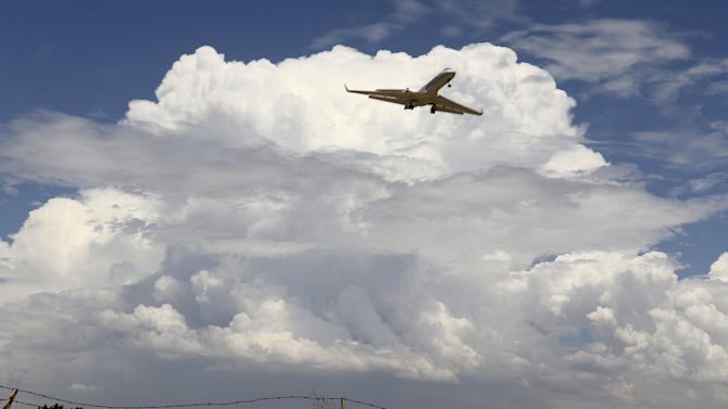 A privet jet comes in for a landing at the Van Nuys airport with huge monsoon storm cells clouds in the skiesduring monsoon rains in the high desert area of Los Angeles  County, California
