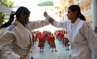 Indian students watch an exhibition of basic Judo skills in Ahmedabad on January 21, 2013. Five men have gone on trial over the fatal gang-rape of student on a bus in Delhi as the victim's father urged the special fast-track court to deliver swift justice and sentence her attackers to hang