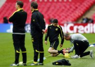 A member of Borussia Dortmund's coaching staff adjusts Robert Lewandowski's boots during a training session ahead of their Champions League Final soccer match against Bayern Munich at Wembley Stadium in London, May 24, 2013.  REUTERS/Michael Dalder (BRITAIN - Tags: SPORT SOCCER)